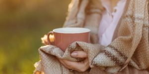 cup on sunset in hand young girl covered with a blanket